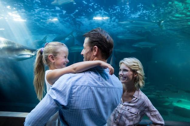 Familie, die hinter einem fischbecken genießt