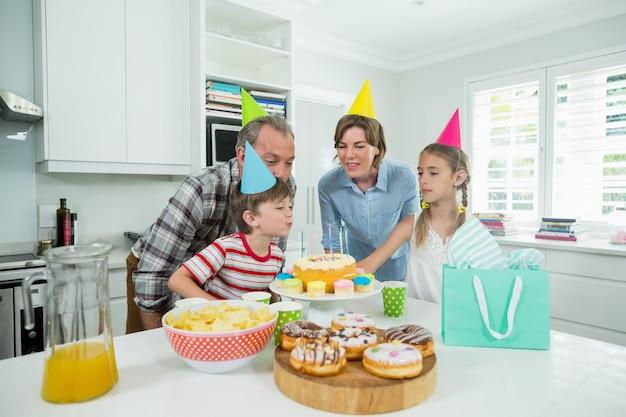 Familie, die ihren sohngeburtstag in der küche feiert