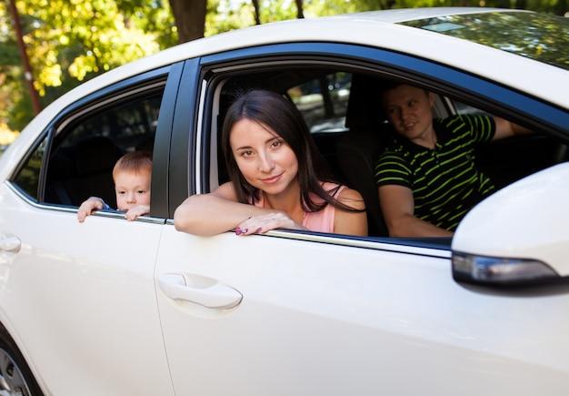 Familie, die im auto heraus schaut fenster sitzt