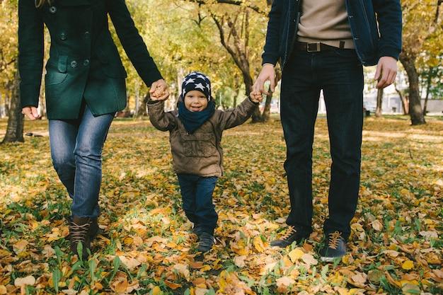 Familie, die im herbstpark glückliches kind mit eltern geht