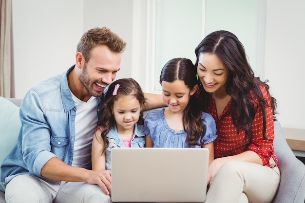 Familie, die im laptop auf sofa lächelt und schaut