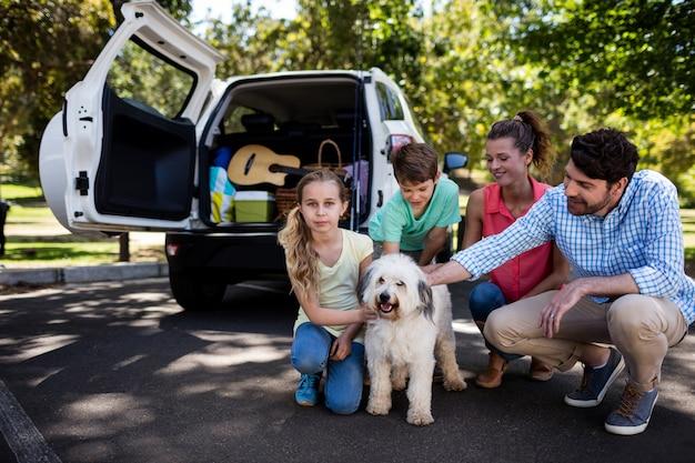 Familie, die im park mit ihrem hund sitzt