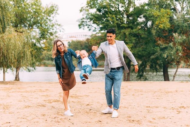 Familie, die im park zusammen nahe einem see spielt