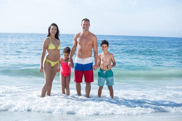 Familie, die im seichten wasser am strand steht