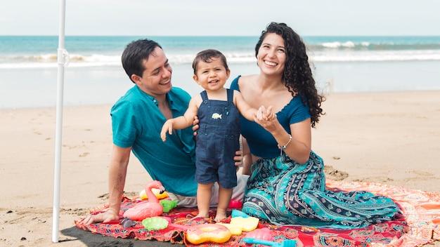 Familie, die im sommer zusammen am strand sitzt