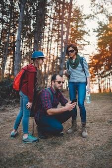 Familie, die im wald wandert und intelligentes telefon verwendet
