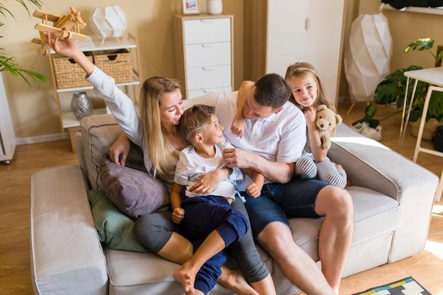 Familie, die im wohnzimmer mit spielwaren spielt