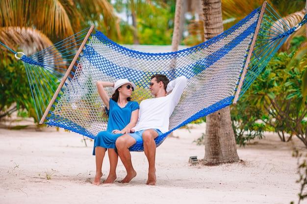 Familie, die in der hängematte am strandurlaub entspannt