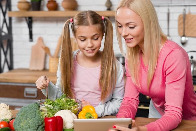 Familie, die in der küche kocht und die tablette betrachtet