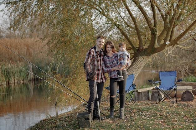 Familie, die in der nähe des flusses an einem fischermorgen sitzt