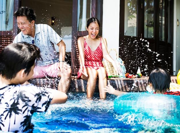 Familie, die in einem pool spielt