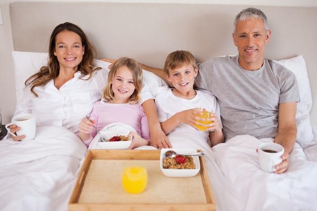 Familie, die in einem schlafzimmer frühstückt
