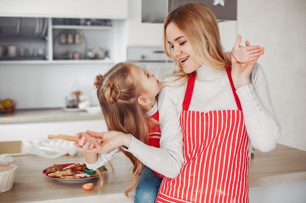 Familie, die in einer küche mit plätzchen sitzt