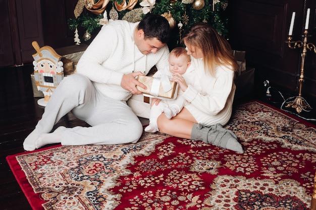 Familie, die in verziertem wohnzimmer aufwirft entzückende frau, mann und baby, die in der gemütlichen weißen gestrickten kleidung trägt.