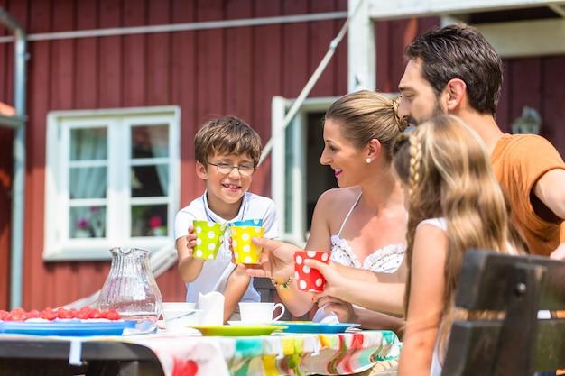 Familie, die kaffee trinkt und kuchen vor haus isst
