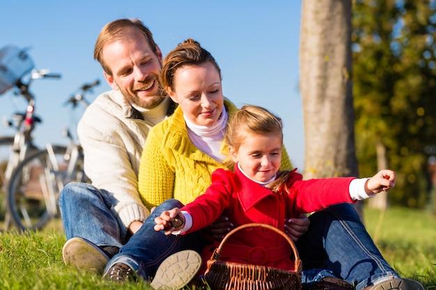 Familie, die kastanien auf fahrradreise sammelt