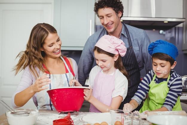 Familie, die lebensmittel in der küche zubereitet