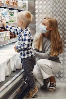 Familie, die lebensmittel kauft. mutter im grauen pullover. frau in einer medizinischen maske. coronavirus-thema.