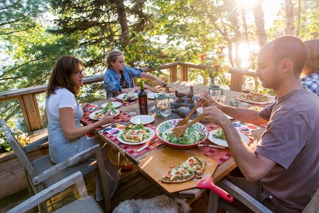 Familie, die mahlzeit auf einer plattform, see des holzes, ontario, kanada isst