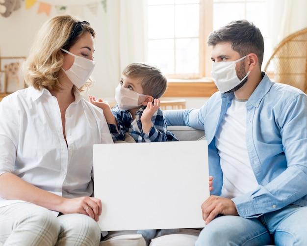 Familie, die medizinische masken drinnen trägt, kopiert raum