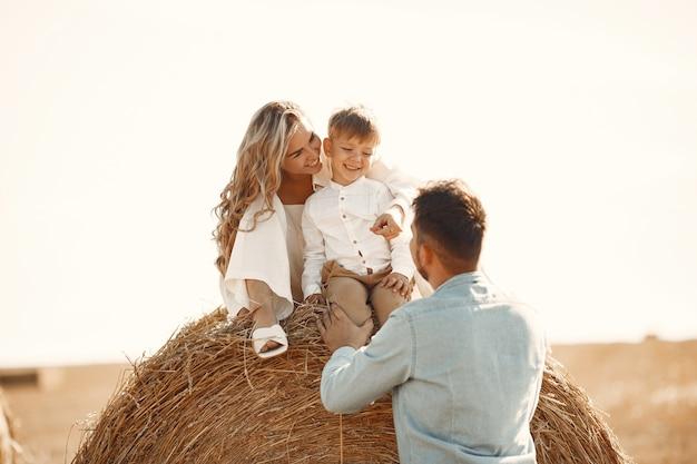 Familie, die mit dem kleinen sohn im weizenfeld auf sonnenuntergang spielt. das konzept der sommerferien. familie verbringt zeit miteinander in der natur.