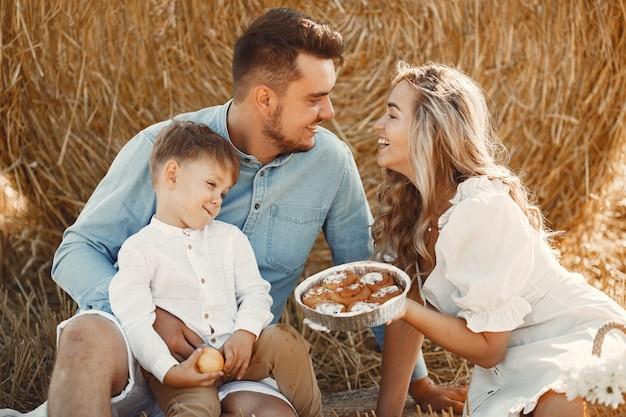 Familie, die mit dem kleinen sohn im weizenfeld auf sonnenuntergang spielt. leute auf einem picknick. familie verbringt zeit miteinander in der natur.