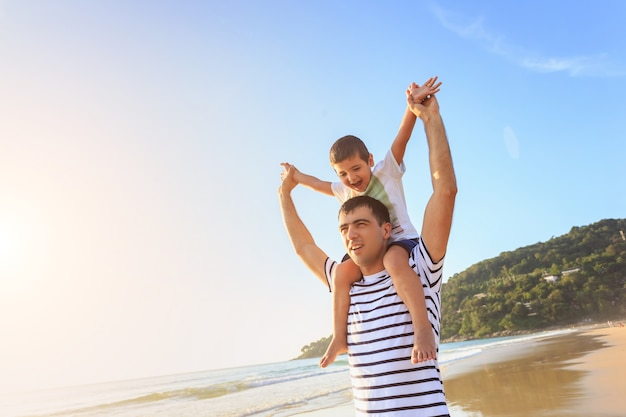 Familie, die mit dem sohn auf dem strand zur sonnenuntergangzeit spielt