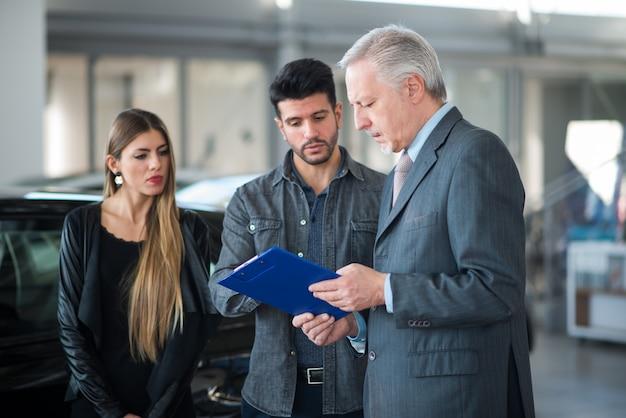 Familie, die mit dem verkäufer spricht und ihr neues auto in einem ausstellungsraum wählt