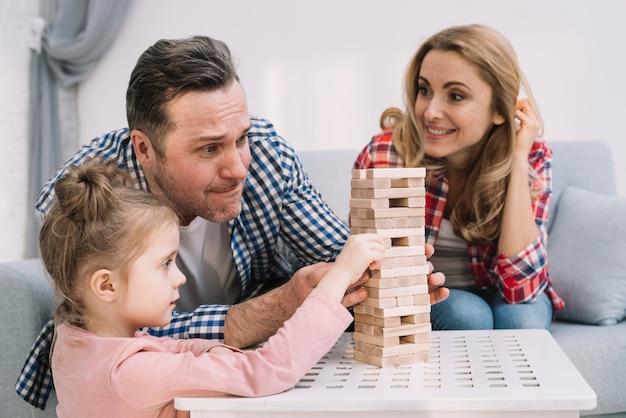 Familie, die mit hölzernem spiel des blockes auf tabelle im wohnzimmer spielt