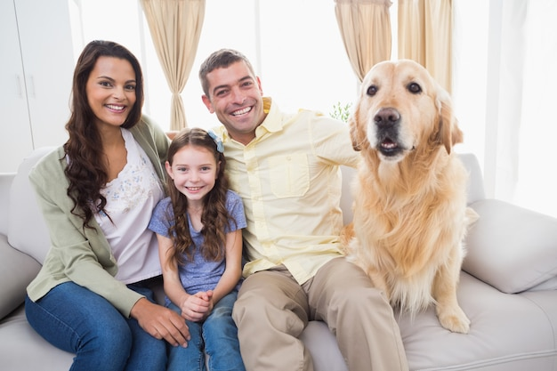 Familie, die mit hund auf sofa sitzt