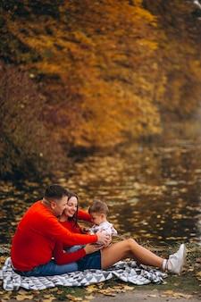 Familie, die mit kleinem sohn am see sitzt