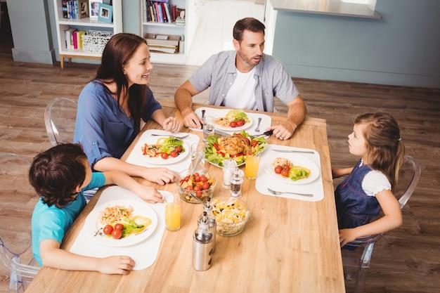 Familie, die mit lebensmittel auf speisetische sich bespricht