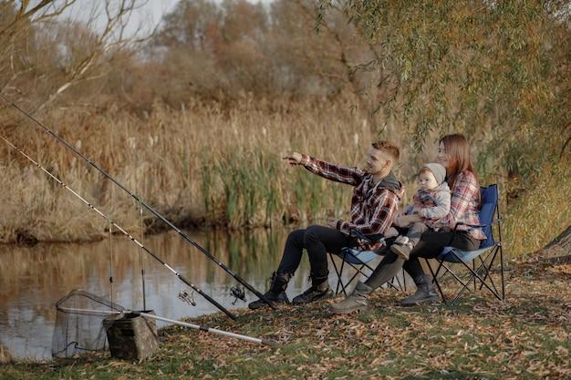 Familie, die nahe fluss in einem morgenfischen sitzt