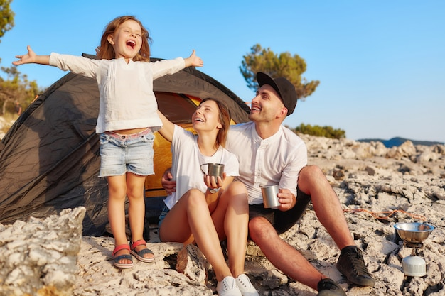 Familie, die nahe zelt, stehendes und händchenhalten des kleinen mädchens oben stillsteht.