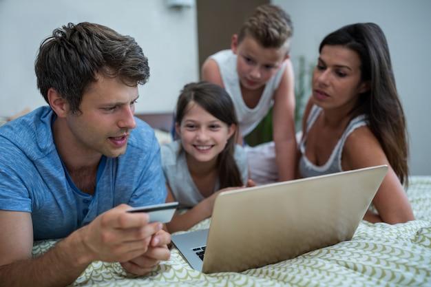 Familie, die online-shopping auf laptop im schlafzimmer tut