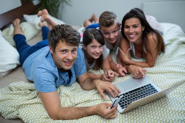 Familie, die online-shopping auf laptop im schlafzimmer zu hause macht