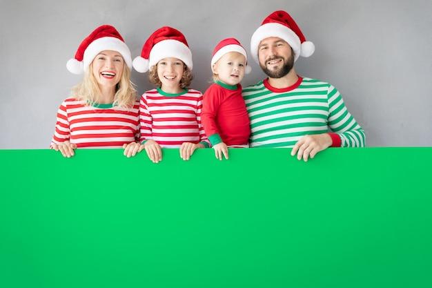 Familie, die pappfahne leer hält. glückliche leute, die zu hause spielen. weihnachtsferienkonzept. platz kopieren.