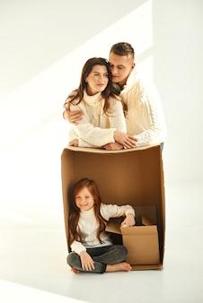 Familie, die pappkartons am neuen zuhause auspackt