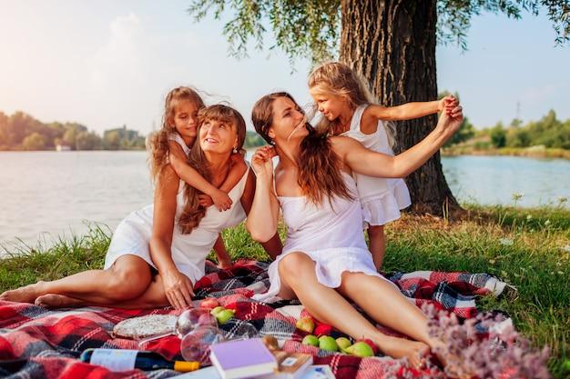 Familie, die picknick am sommerfluss bei sonnenuntergang hat. mutter, großmutter und kinder umarmen sich. frauentag