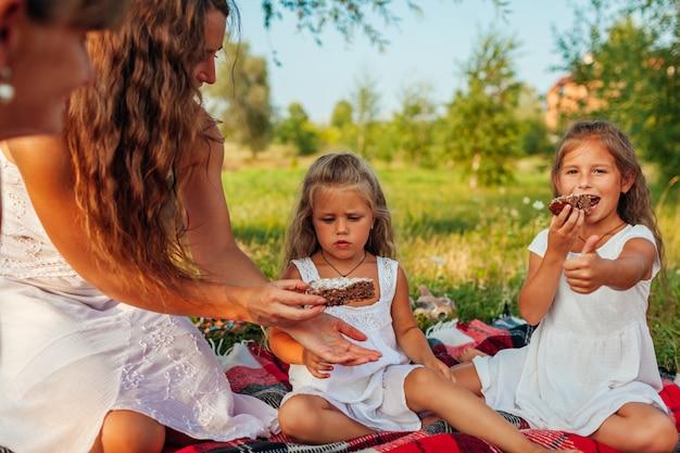 Familie, die picknick durch sommerfluß bei sonnenuntergang hat, mutter, großmutter und kinder, die kuchen teilen,