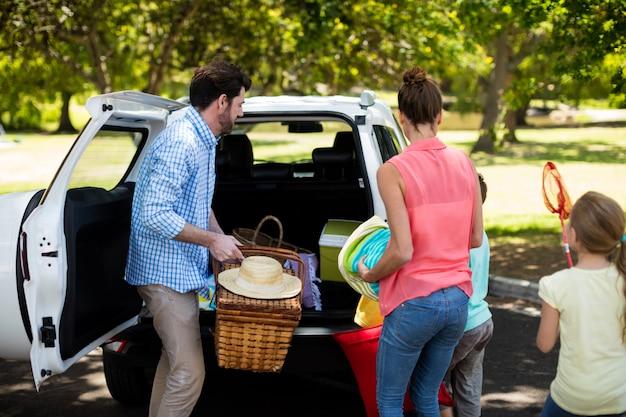 Familie, die picknickartikel in kofferraum legt