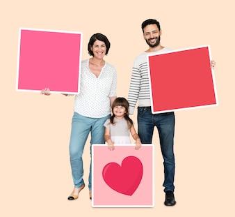 Familie, die rosa quadratische Bretter hält