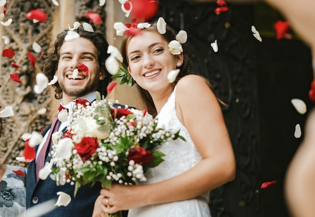 Familie, die rosafarbene blumenblätter an der gerade vermählten braut und am bräutigam wirft