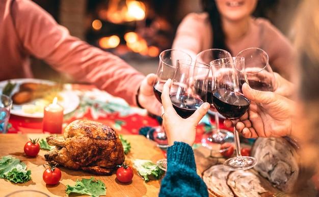 Familie, die rotwein röstet und spaß an der weihnachtsabendessenparty hat
