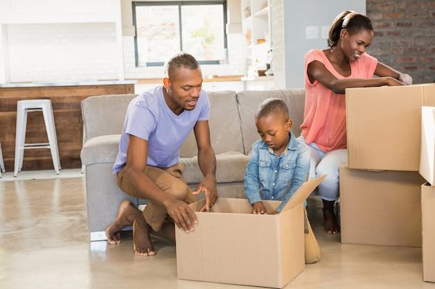 Familie, die sachen im neuen haus im wohnzimmer auspackt