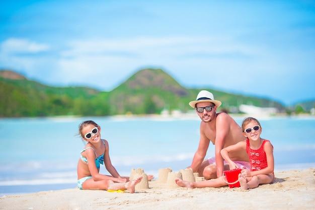 Familie, die sandburg am tropischen weißen strand macht. bringen sie und zwei mädchen hervor, die mit sand auf tropischem strand spielen