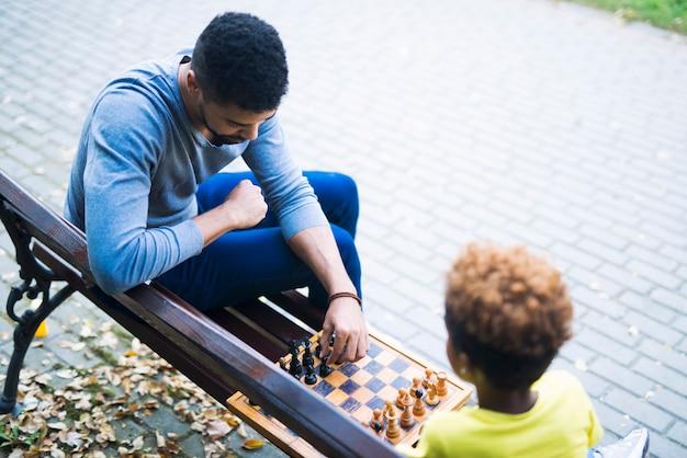 Familie, die schachspiel auf der bank im park spielt
