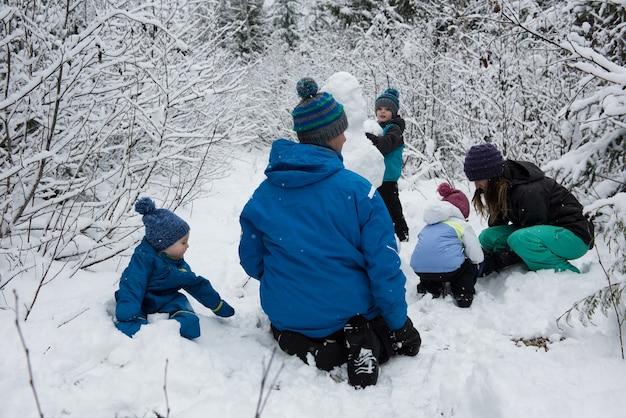 Familie, die schneemann am verschneiten tag macht