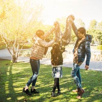 Familie, die schöne glückliche bewegungen im park hat