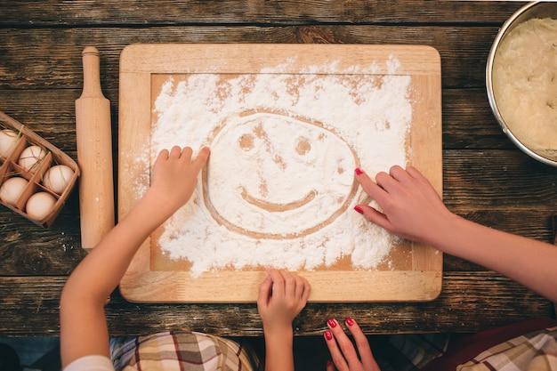 Familie, die selbst gemachte kuchen-, mutter- und tochterhände im mehl auf einer tabelle, draufsicht kocht.